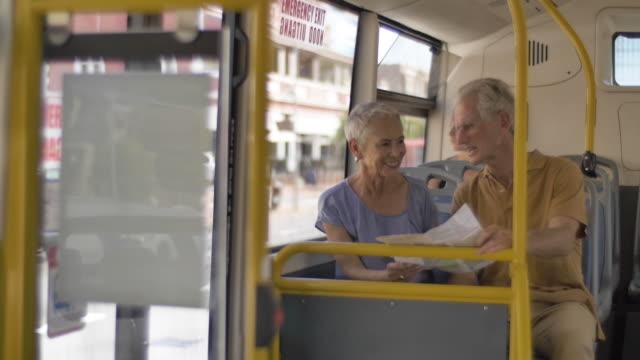 elderly couple look at map on bus, medium shot - public transport stock videos & royalty-free footage