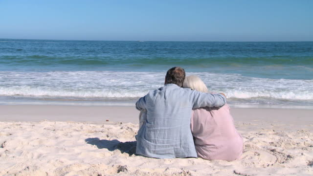 WS Elderly couple looking at ocean sitting on beach / Cape Town, Western Cape, South Africa