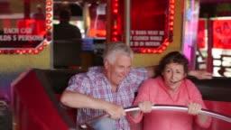 Elderly Couple On Waltzer At Funfair