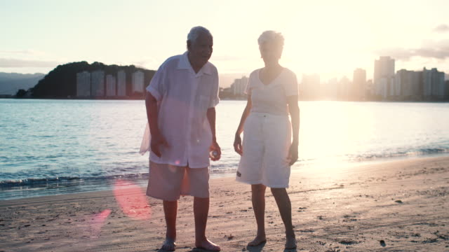 elderly couple playing cricket at the beach - senior men stock videos & royalty-free footage