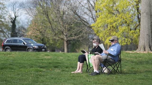 vídeos de stock e filmes b-roll de elderly couple reads druid hill park wearing masks baltimore maryland - equipamento fotográfico