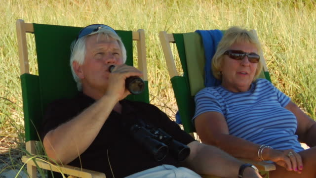 cu, elderly couple relaxing on beach, north truro, massachusetts, usa - binoculars stock videos & royalty-free footage