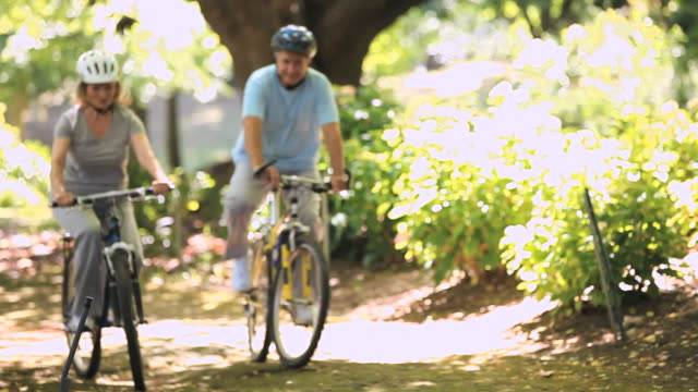 ms pan elderly couple riding bikes in park/ cape town, western cape, south africa - athleticism stock videos & royalty-free footage