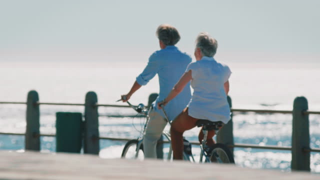 Elderly couple riding tandem bicycle on promenade