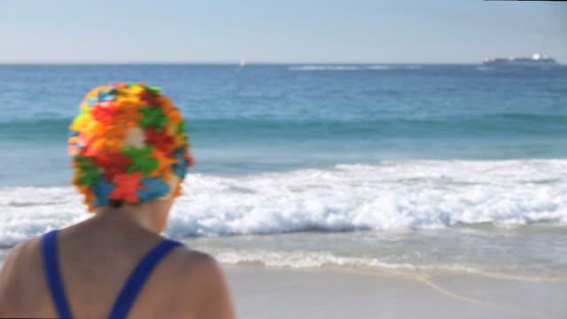 ws elderly couple running to sea on beach / cape town, western cape, south africa - 水泳パンツ点の映像素材/bロール