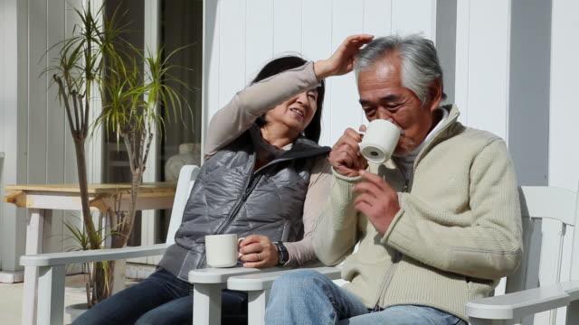 ms elderly couple sitting on chair talking each other  / fujikawaguchiko, yamanashi, japan - アクティブシニア点の映像素材/bロール