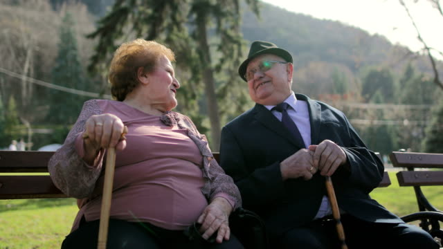 elderly couple sitting on the bench in the spa park.60 years in marriage - corporatura larga video stock e b–roll
