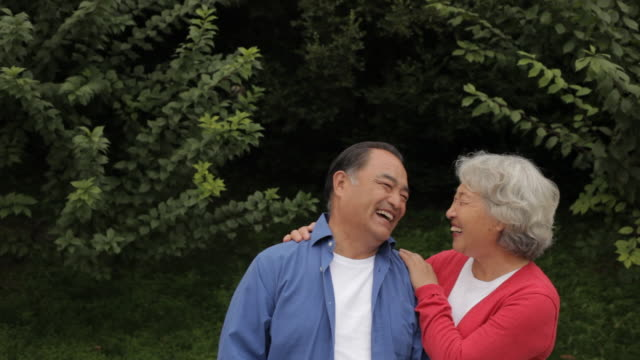 MS Elderly couple smiling together in park / China