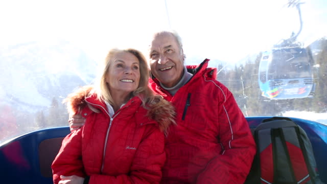 elderly couple taking the gondola to theo top of the mountain - älteres paar stock-videos und b-roll-filmmaterial