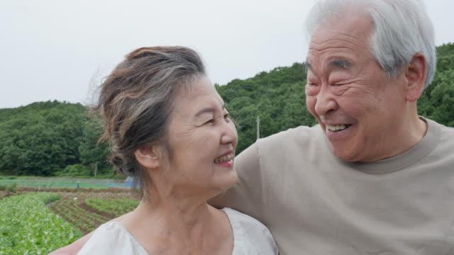 vídeos de stock, filmes e b-roll de elderly couple talking together at the agricultural field - jovem de espírito