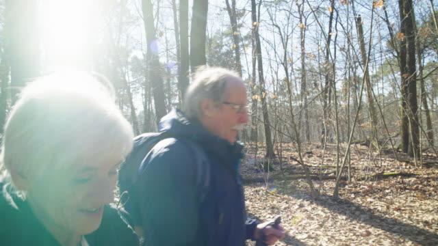 stockvideo's en b-roll-footage met ouderen paar praten tijdens het wandelen in het bos - wandelen lichaamsbeweging