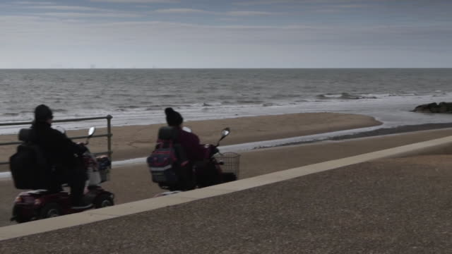 elderly couple travel along seafront in cleveleys lancashire on their mobility scooters during coronavirus lockdown - tourist resort stock videos & royalty-free footage