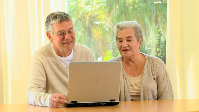 stockvideo's en b-roll-footage met elderly couple using a laptop / cape town, western cape, south africa - oudere internetgebruiker