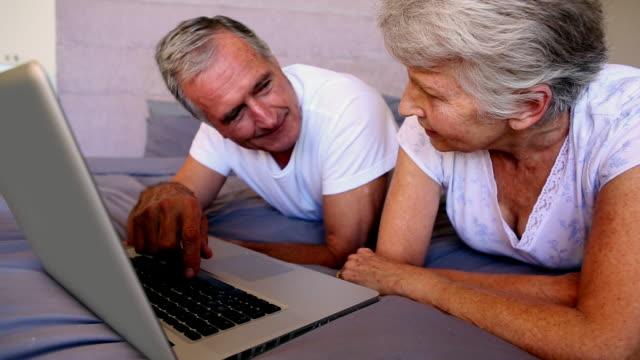 vídeos de stock e filmes b-roll de elderly couple using laptop together - idoso na internet