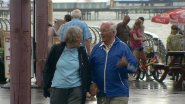 elderly couple walk hand in hand along blackpool pier - couple relationship stock videos & royalty-free footage