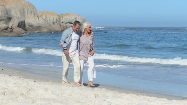 WS PAN Elderly couple walking along beach / Cape Town, Western Cape, South Africa