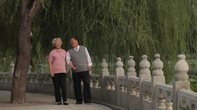 vidéos et rushes de ws elderly couple walking through park together / china - senior men