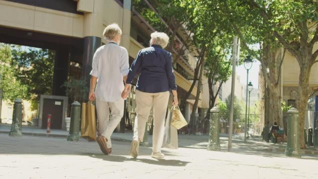 vídeos de stock e filmes b-roll de elderly couple with shopping bags crossing street - saco de compras