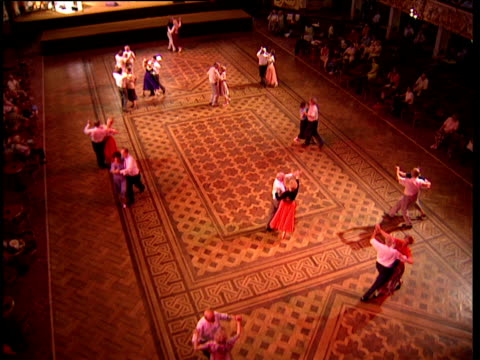 Elderly couples dance across mosaic floor of ballroom