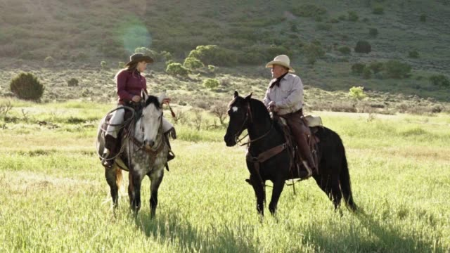 elderly cowboy and young cowgirl riding trough the field meadow - non urban scene stock videos & royalty-free footage