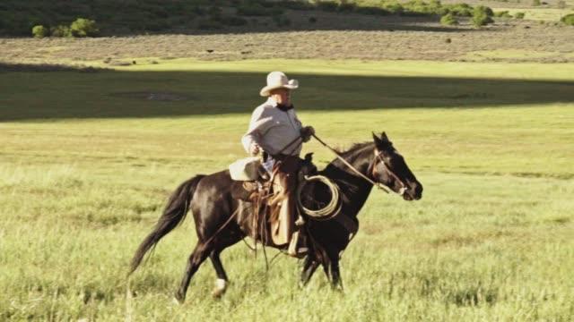 stockvideo's en b-roll-footage met ouderen cowboy op zijn paard in de bergen met een sunburst achter hem - prairie