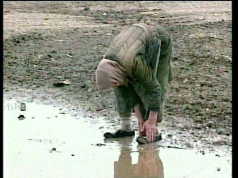 Elderly female survivor of bombings uses puddle to clean shoes Grozny; 18 Feb 00