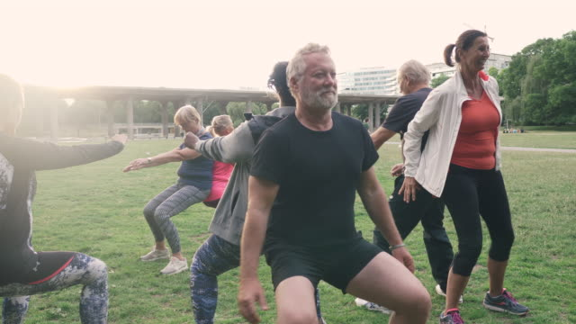 vídeos y material grabado en eventos de stock de elderly friends doing back to back squats in park - 60 64 años