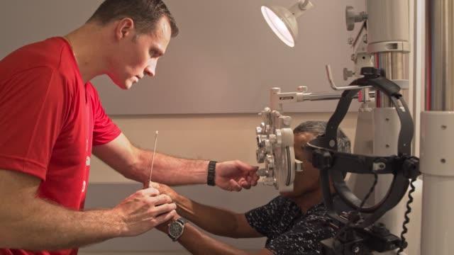 elderly gentleman check his eyesight - lens optical instrument stock videos & royalty-free footage