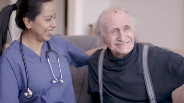 vídeos y material grabado en eventos de stock de anciano caballero con enfermera durante la visita de cuidado en el hogar - cuidado de personas de la tercera edad