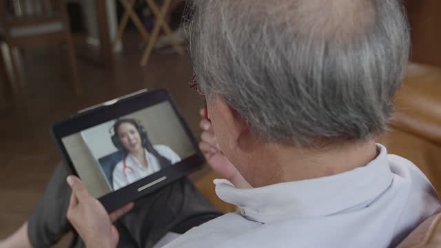 elderly grandfather holding a bottle of medicine to consult a doctor using a tablet as a video call to reduce the distance between them and reduce the chance of transmitting infection - female doctor stock videos & royalty-free footage