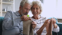 Elderly grandfather learning knitting helping older wife at home