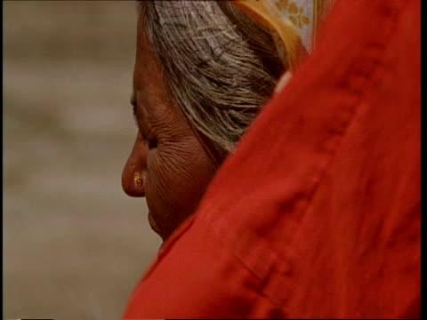 cu elderly gujarat, indian woman's face in profile, headscarf blowing in breeze, gujarat, india - グジャラート州点の映像素材/bロール