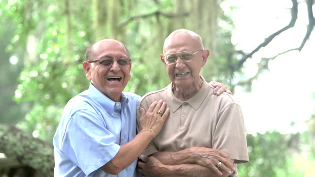 elderly hispanic man and adult son in the park - arm in arm stock videos and b-roll footage