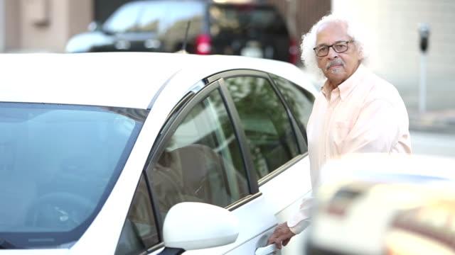 高齢のヒスパニック系の男性が駐車中の車に乗り込む - 入る点の映像素材/bロール