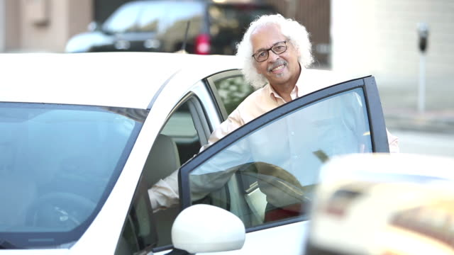 elderly hispanic man getting into parked car - white hair stock videos and b-roll footage