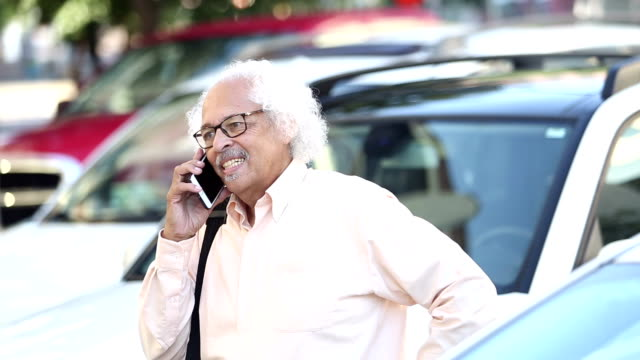 elderly hispanic man standing in parking lot on phone - white hair stock videos and b-roll footage