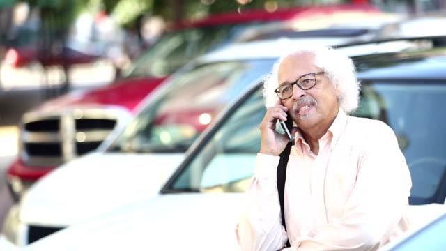 elderly hispanic man walking in parking lot on phone - white hair stock videos and b-roll footage