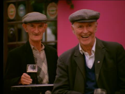 2 elderly irish men drinking ale, smiling + laughing - european culture stock videos & royalty-free footage
