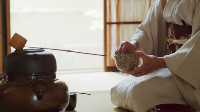 vídeos de stock, filmes e b-roll de anfitrião japonês idoso da cerimónia do chá que prepara implementa - washitsu