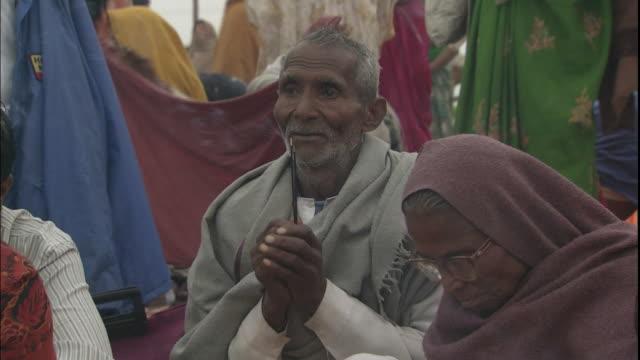 Elderly Kumbh Mela pilgrim sits and prays with incense sticks, Allahabad, Uttar Pradesh, India