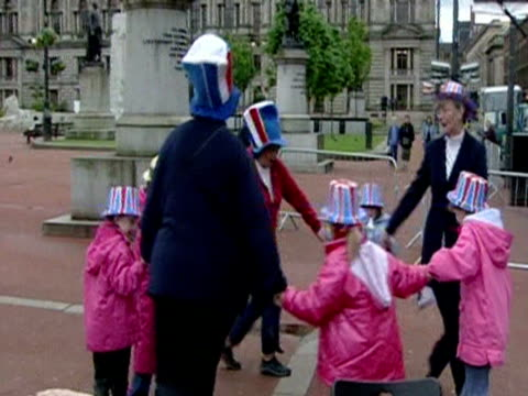 stockvideo's en b-roll-footage met elderly ladies and young children wearing union jack hats dance in george square glasgow waiting for the queen during her golden jubilee royal tour - 50 jarig jubileum