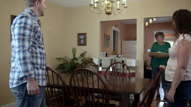 vídeos de stock e filmes b-roll de elderly lady adorning dining room table with young man and woman. - fazer um favor