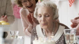 Elderly Lady Blowing Off Birthday Candles