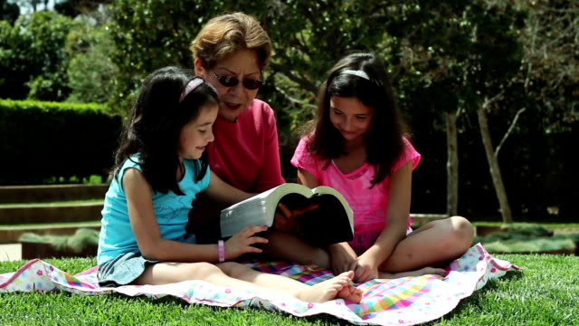 elderly lady reads to young girls outdoors - bible stock videos & royalty-free footage