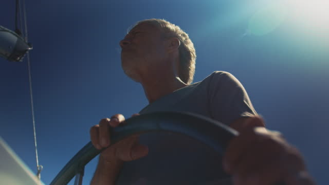 elderly male traveling in yacht on sunny day - helm stock videos and b-roll footage