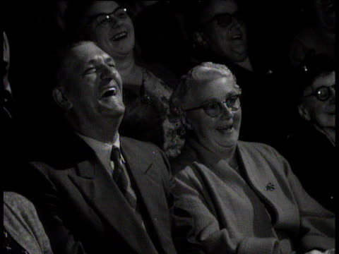 Elderly man and woman chuckling in audience