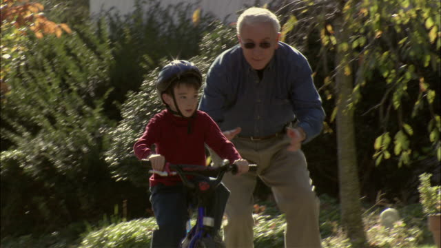 vídeos y material grabado en eventos de stock de ms ts elderly man helps young boy learn to bicycle / long island, new york, usa - abuelo