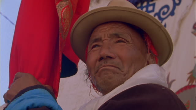 elderly man holds prayer flag and observes parade available in hd. - tibet stock videos & royalty-free footage