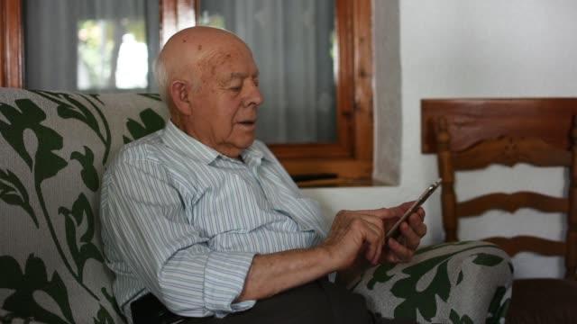 vídeos de stock e filmes b-roll de elderly man is using his smartphone at home - 70 anos