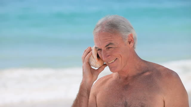 CU Elderly man listening to seashell on beach / Cape Town, Western Cape, South Africa